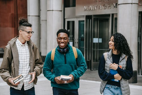 Group of smiling multiracial students with books strolling near building