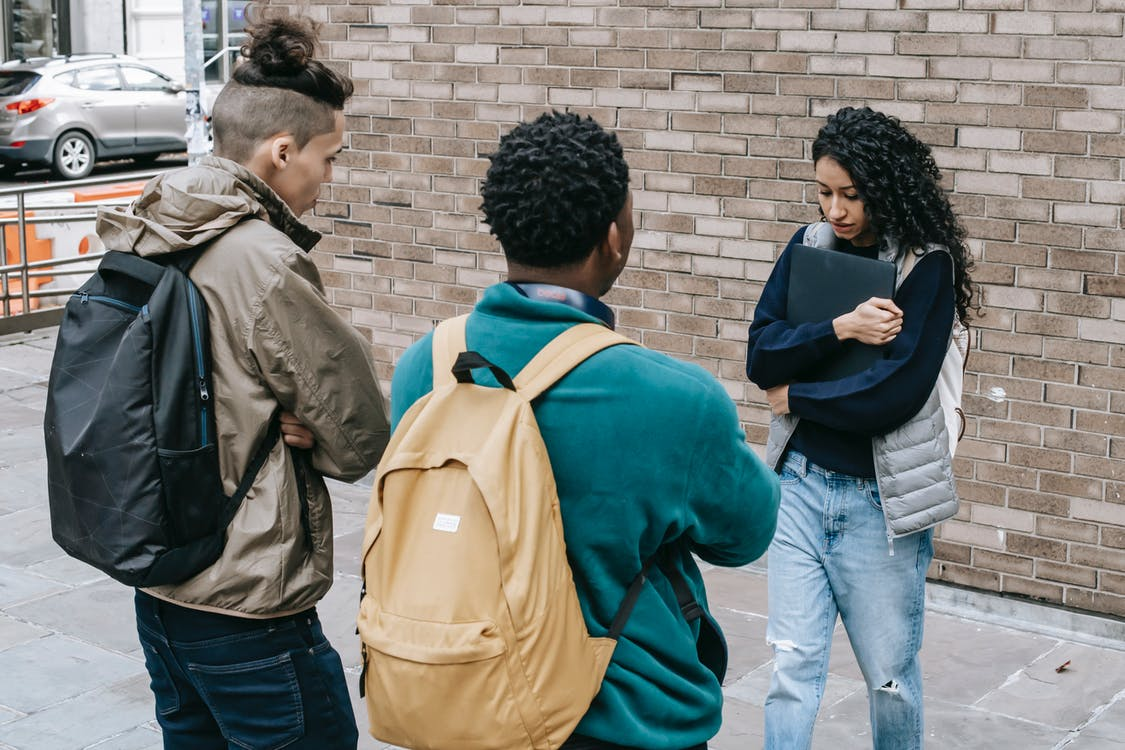 Young multiracial male friends with backpacks offending female with folder on city street near brick wall in daylight
