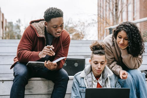 Young multiethnic friends in warm clothes sitting on stairs in campus while preparing for exam and taking notes in notepad with pen and browsing on laptop in daytime