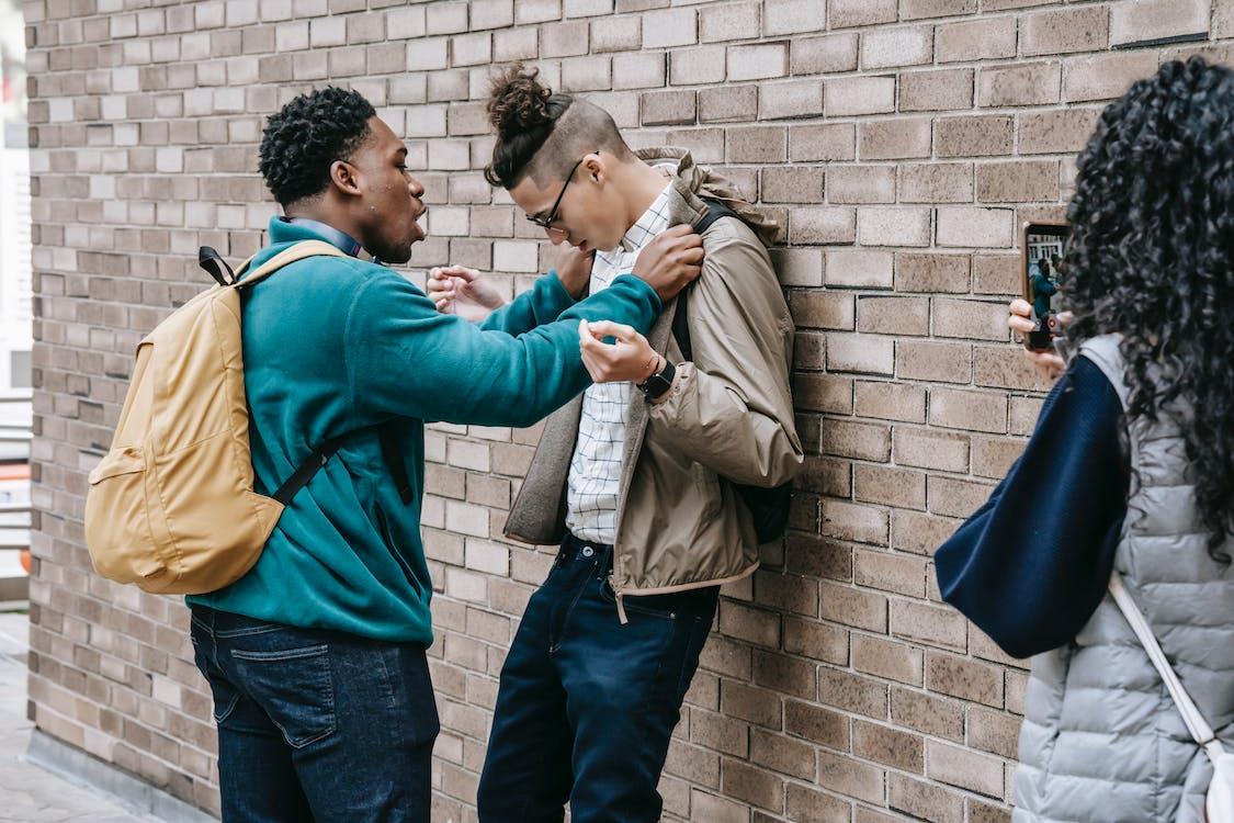 Multiethnic students having conflict on street