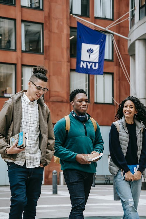 Smiling young multiracial students in casual clothes with backpacks talking while strolling in New York City with books and headphones near university building with flag in daytime