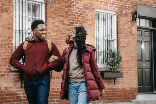Smiling young multiracial friends in warm outfit and backpacks strolling on city street near building with brick wall and windows near door in daylight while looking at each other