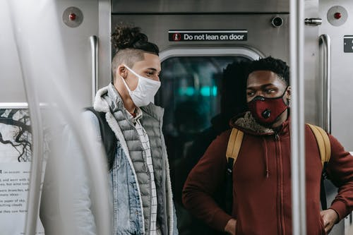 Multiracial friends in masks standing in subway train