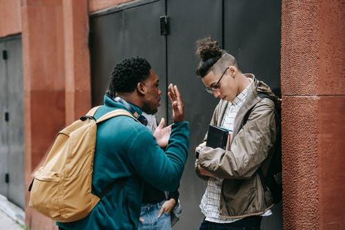 Annoyed black man arguing with friend on city street