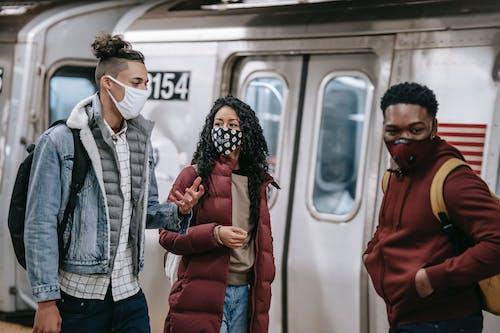 Diverse partners in masks speaking on metro