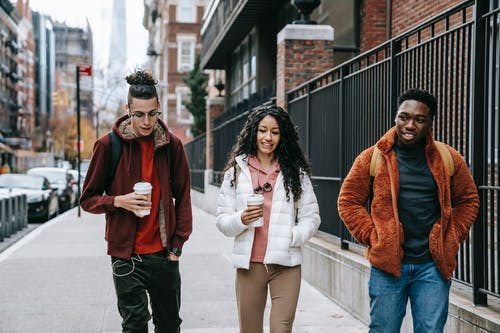 Young glad multiracial partners with hot drinks to go strolling on urban pavement in daytime