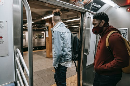 Anonymous diverse passengers with rucksacks getting off subway