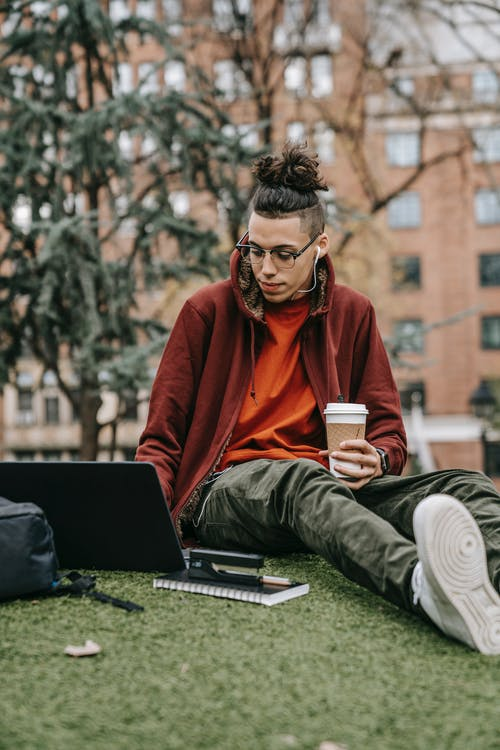 Young man with takeaway hot drink browsing internet on portable computer while studying in city park