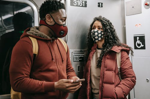 Multiethnic couple in masks with smartphone talking on subway