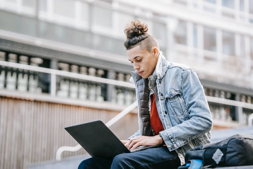 Young focused man in casual wear with modern haircut surfing internet on netbook while studying on urban staircase