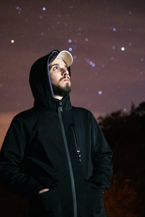 Man in Black Hoodie Standing during Night Time