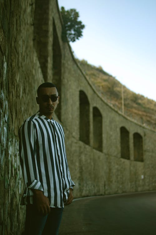 Man in Black and White Striped Long Sleeve Shirt Wearing Black Sunglasses Standing Near Brown Concrete