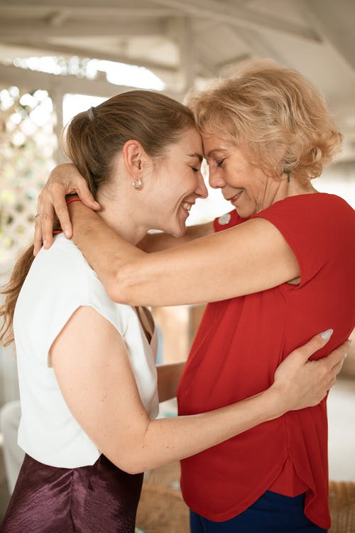 Woman in White Shirt Kissing Woman in Red Shirt