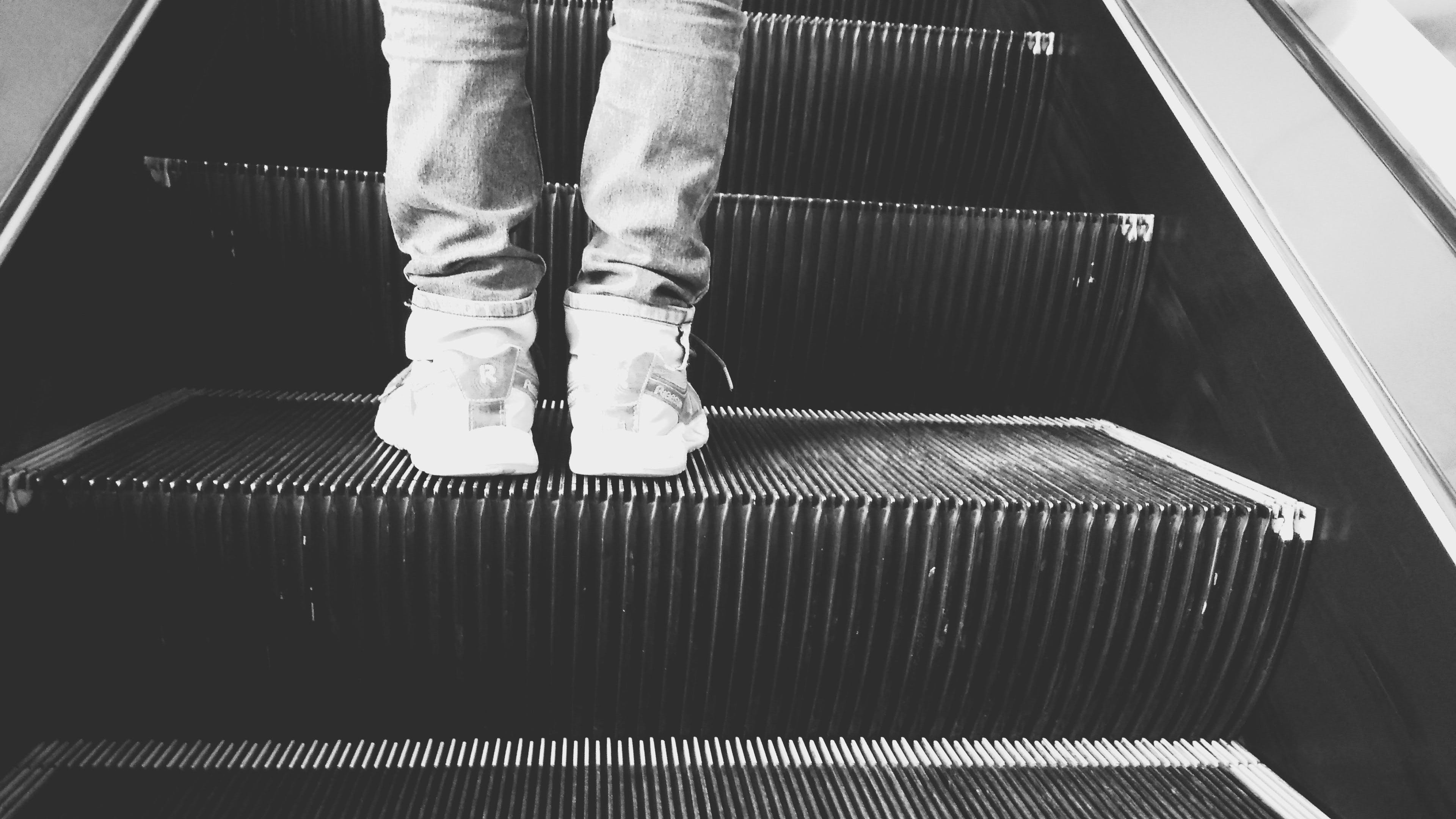 Grayscale Photo of Person Standing on Esclator
