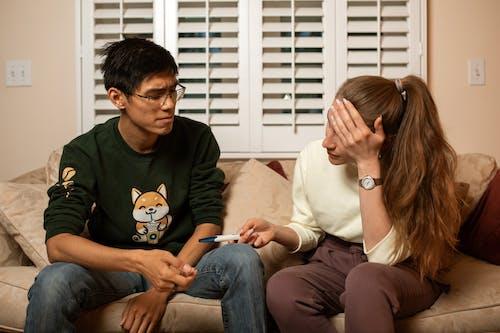 Man in Black Framed Eyeglasses Sitting Beside Woman in White Crew Neck Shirt