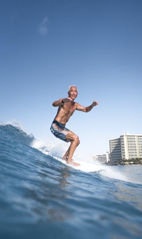 Man on surfboard in sea near city