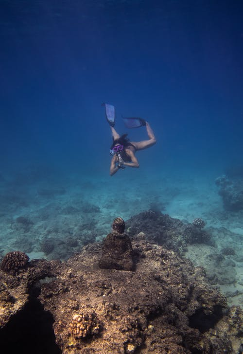 Unrecognizable woman diving underwater above coral