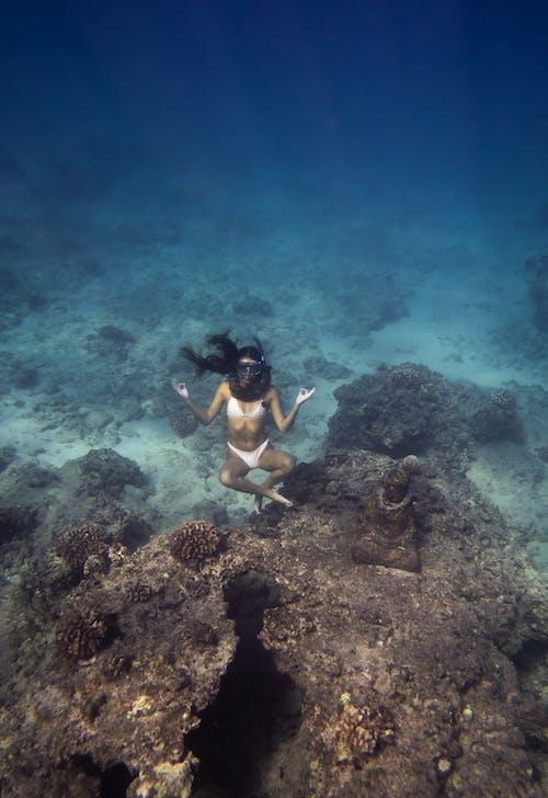 Unrecognizable female diver meditating underwater