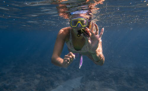 Unrecognizable woman showing seashell while swimming underwater