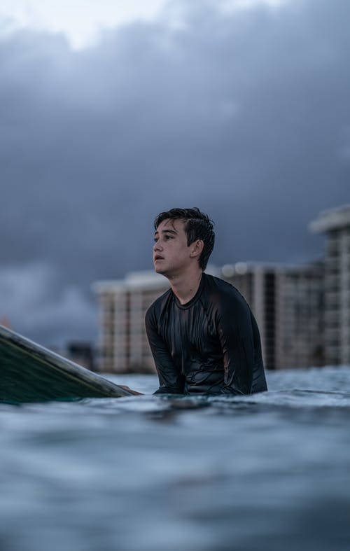 Young man surfer in wetsuit waiting for wave on board in sea under cloudy sky near city