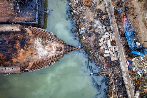 Aerial view of abandoned rusty ship moored in sea near dirty coast full of garbage in industrial area in sunlight