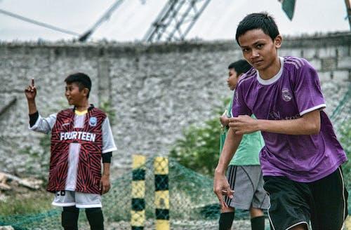 Ethnic boys playing football on street