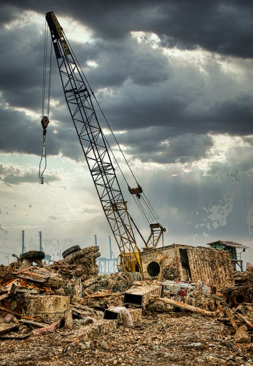 Aged abandoned scrap yard with old rusty lifting crane under cloudy sky illuminated by sunlight in daytime