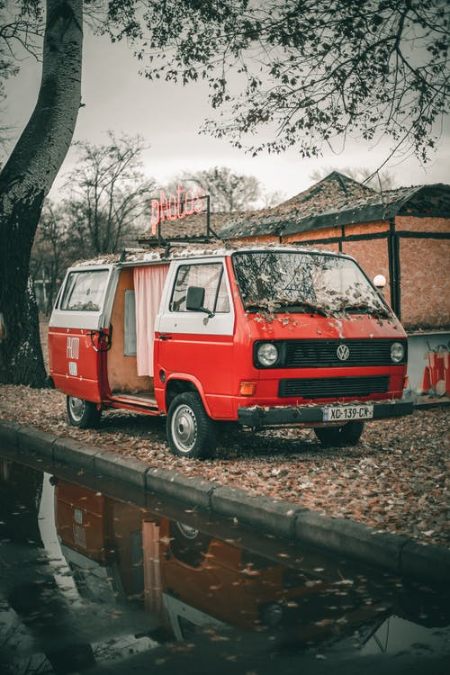Red vintage photo van with opened door parked on lawn with fallen leaves on ground near small cottage and asphalt road with puddle near trees in daylight in town street under gray cloudy sky