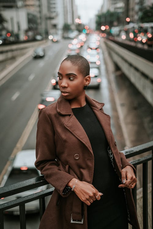 Stylish black woman leaning on fence in city