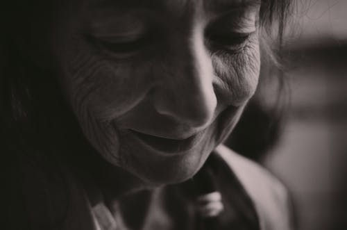 Black and white closeup of crop smiling senior female face with closed eyes