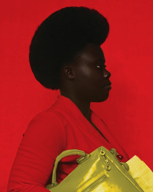 Side view of African American female with yellow bag looking away while standing against red background