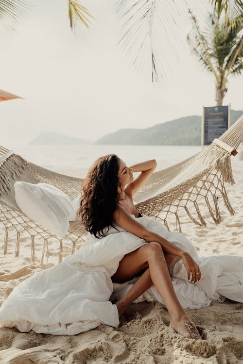 Kumsalda Beyaz Tekstil üzerinde Oturan Beyaz Elbiseli Kadın