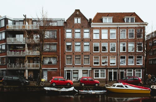 Exterior of aged brick residential houses located on embankment near cars and boats