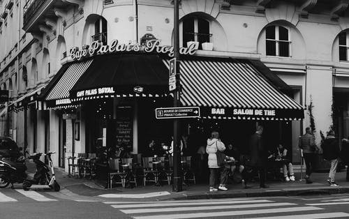 Black and white of exterior of old building with cafe full of people located on intersection of roads