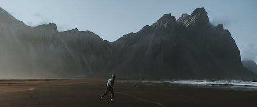 Человек в белой рубашке, идущий по пляжу