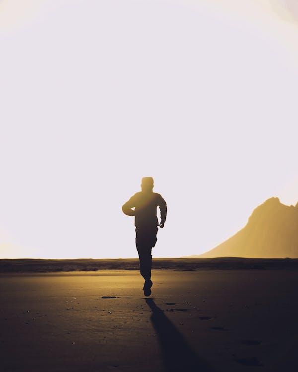 Mann In Der Schwarzen Jacke, Die Auf Braunem Sand Steht