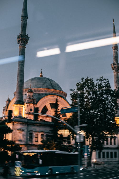 Aged mosque on street with bus in late evening