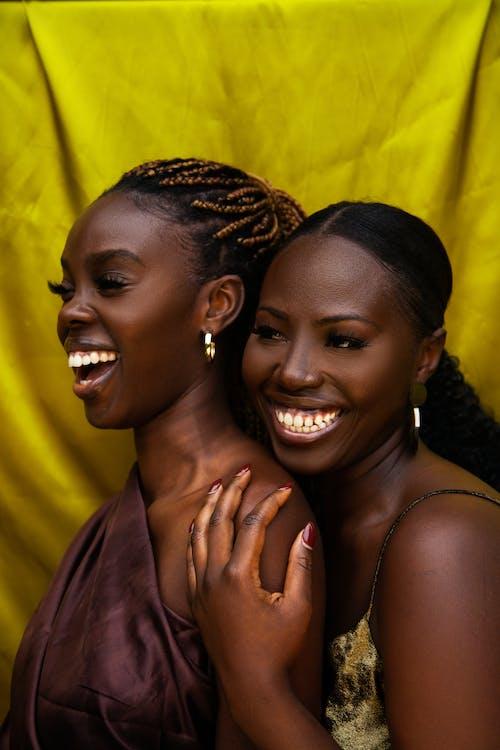 Happy black women laughing while hugging