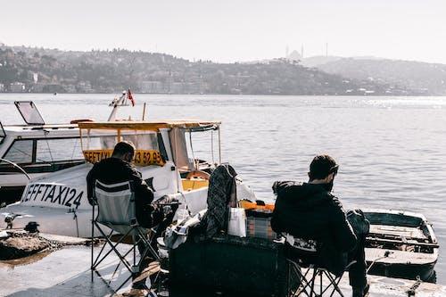 Unrecognizable men sitting on pier