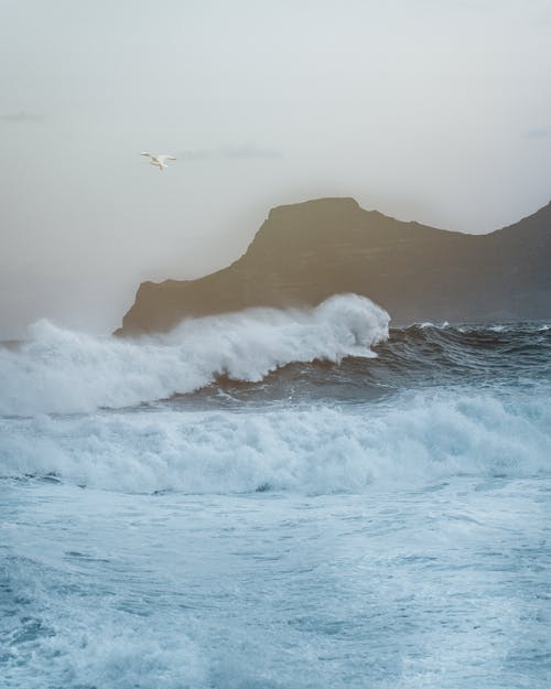 Picturesque view of foamy ocean with waves crashing near rough rocky cliff against cloudy sky