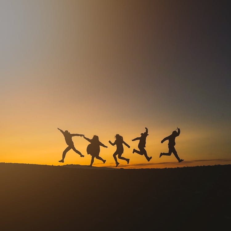 Unrecognizable happy people jumping in sunset