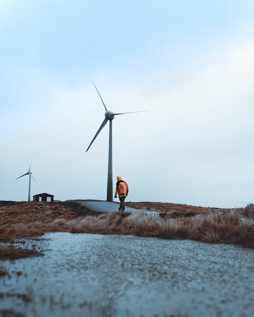 橙色襯衫站在風車附近的棕色草地上的人