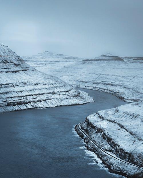 Frozen river stream flowing in mountainous terrain