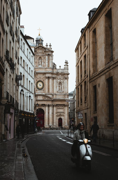 Old classic buildings located on narrow paved street with pedestrians in European city