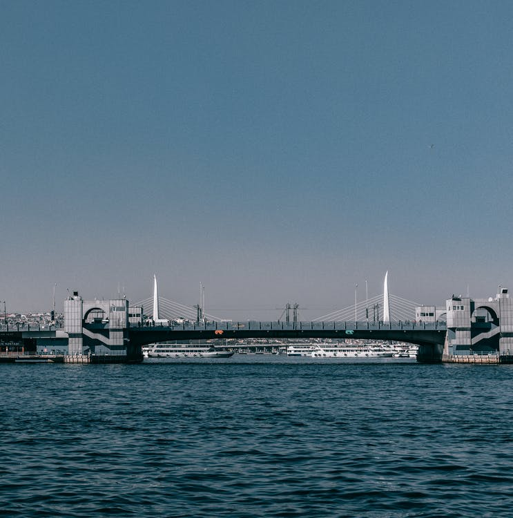 Modern bridge over Bosphorus bay with rippling water located against blue sky in coastal area of Istanbul city in Turkey