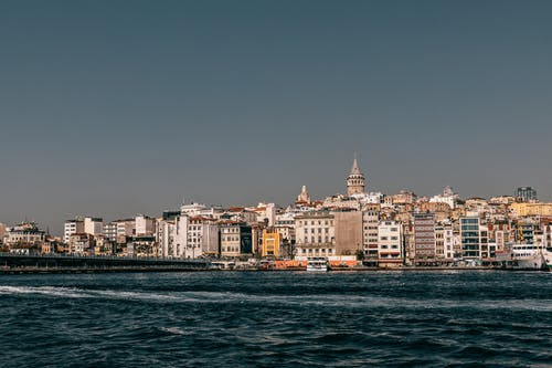 Rippling water of Bosphorus bay with Galata bridge and residential buildings with tower on background in Istanbul city against blue sky