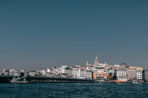 Modern bridge crossing calm sea against residential building and Galata tower of coastal city in Istanbul in turkey against blue sky