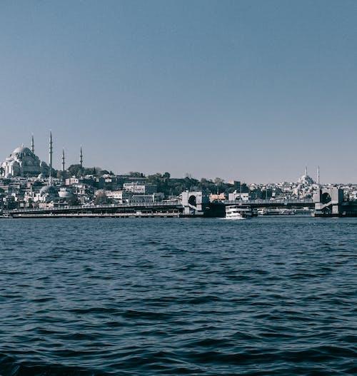 Distant Galata bridge over Bosphorus strait located against coastal city with Hagia Sophia in Istanbul in Turkey against blue sky