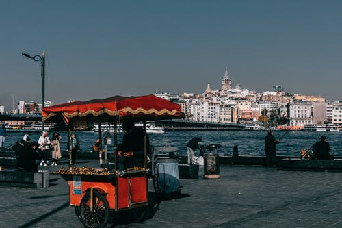 Red food truck located on crowded quay near sea against coastal city with buildings and Galata tower in Istanbul in Turkey