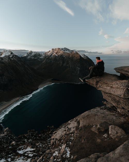 Человек в черной куртке сидит на скале возле водоема